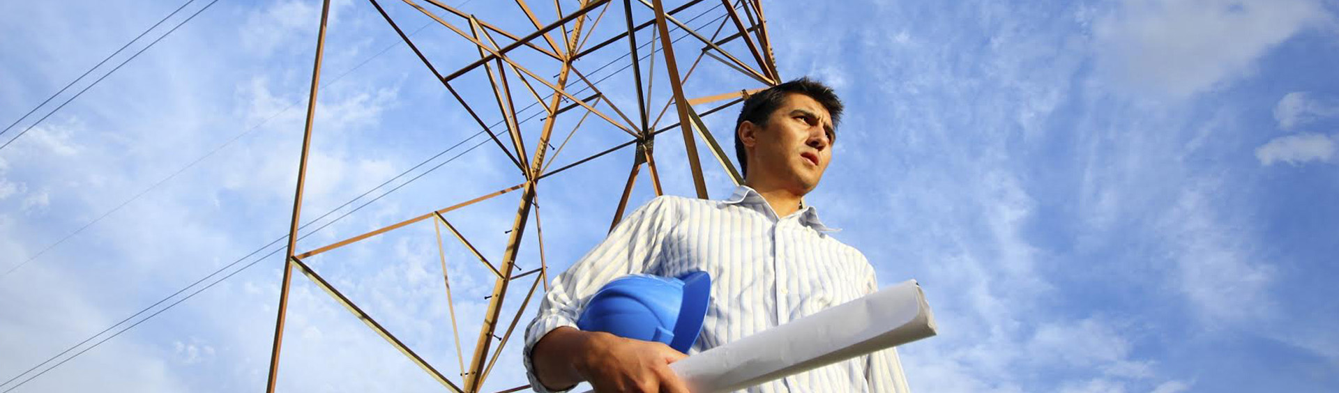 Man Standing Under Powerlines and Holding Construction Plans